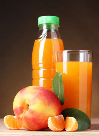 Nectarine, juice glass and bottle on wooden table on brown background Stock Photo - 10899928