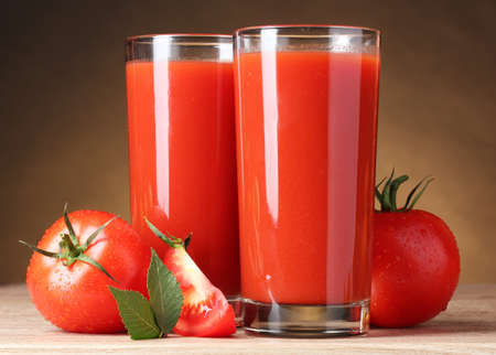 Tomato juice in glasses and tomato on wooden table on brown background