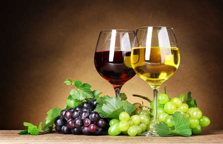 white wine glass: Glasses of wine and grapes on yellow background Stock Photo