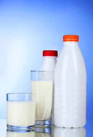 Tasty milk in glass and bottle on blue background photo