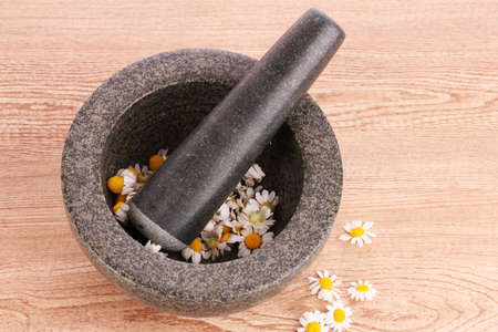 chamomile flowers in a mortar on brawn photo