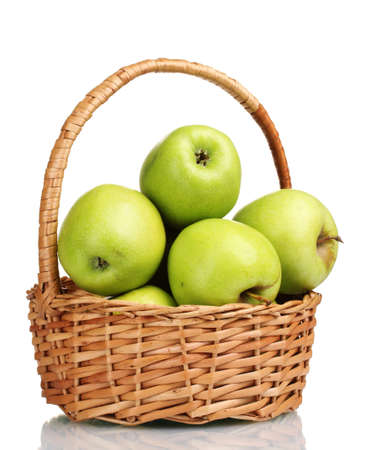 canastas con frutas: jugosas manzanas verdes en la cesta aislada en blanco Foto de archivo