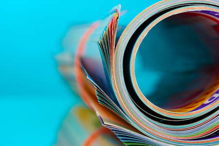 Rolled up magazines on blue background