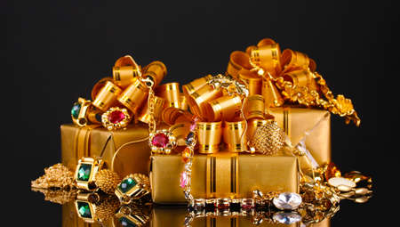 Various gold jewellery and gifts on black background Stock Photo - 11037200