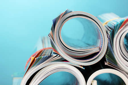 Rolled up magazines on blue background photo