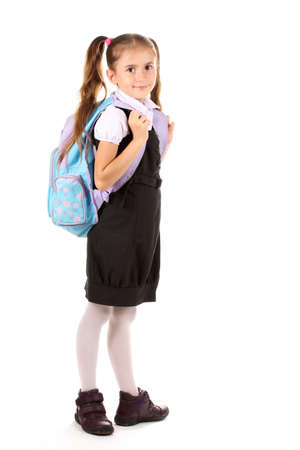schooltime: Portrait of beautiful little girl in school uniform with backpack. Isolated on white