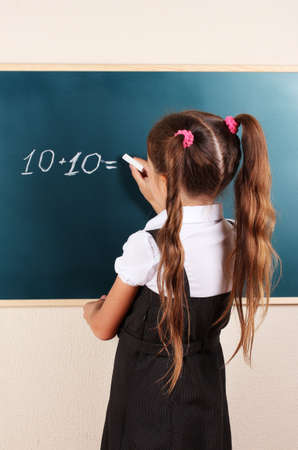beautiful little girl writing on classroom board photo