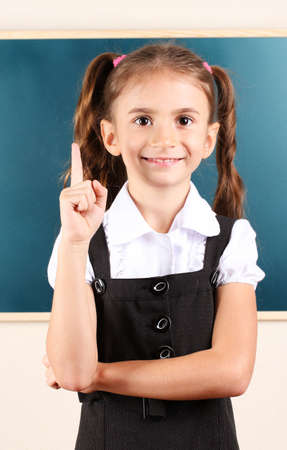 beautiful little girl standing near blackboard in the classroom photo