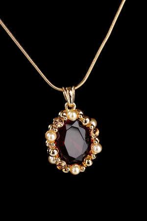 diamond necklace: beautiful golden pendant with gem on black background