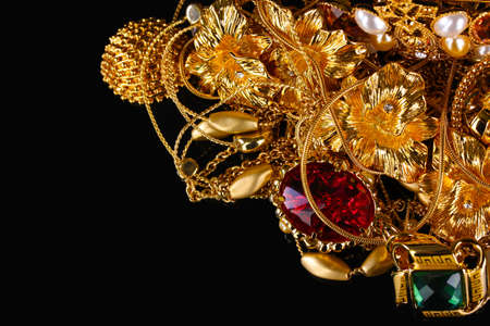 Various gold jewellery on black background photo