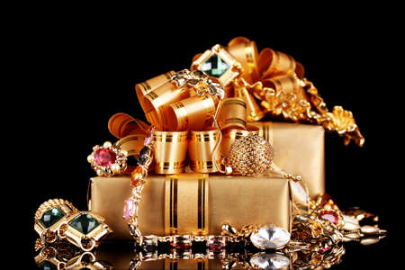 Various gold jewellery and gifts on black background Stock Photo - 11037276