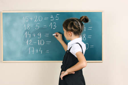 uniform student: beautiful little girl writing on classroom board