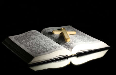 Russian open holy bible with wooden cross on black backround photo