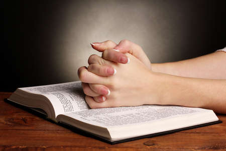 religious text: Hands folded in prayer over open russian Holy Bible on black background