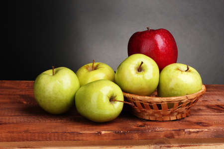 juicy sweet apples in basket on wooden table on gray background photo