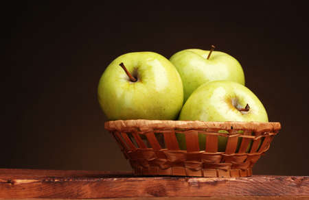 juicy green apples in basket on wooden table on brown background photo