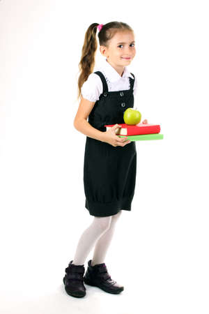 beautiful little girl in school uniform, books and apple isolated on white Stock Photo