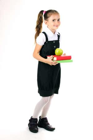 hermosa niña en uniforme escolar, libros y una manzana aislada en blanco Foto de archivo - 11122479
