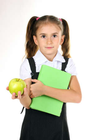 Girl School: beautiful little girl in school uniform, book and apple isolated on white