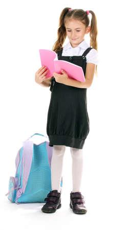 niño con mochila: Retrato de hermosa niña en uniforme escolar con mochila y portátil aislado en blanco