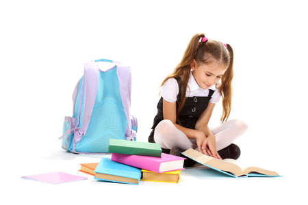 schoolgirls: beautiful little girl, books and a backpack isolated on white