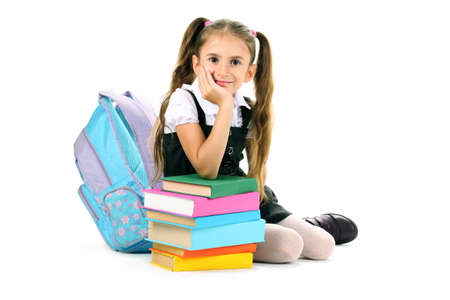 beautiful little girl, books and a backpack isolated on white photo