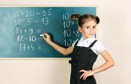 beautiful little girl writing on classroom board Stock Photo - 11122711