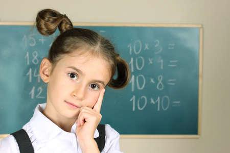 beautiful little girl standing near blackboard in the classroom Stock Photo - 11122713