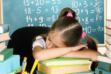 little schoolgirl sleep in classroom near blackboard photo
