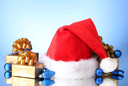 Beautiful Christmas hat, gifts and Christmas balls on blue  background Stock Photo - 11123076