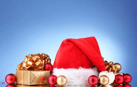 Beautiful Christmas hat, gifts and Christmas balls on blue  background Stock Photo - 11123096