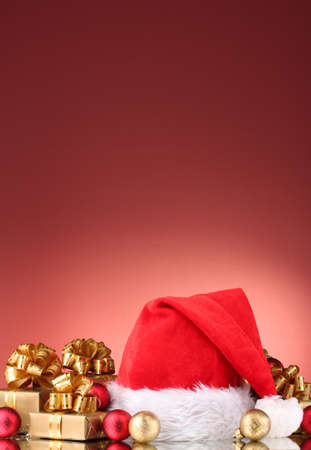 Beautiful Christmas hat, gifts and Christmas balls on red  background Stock Photo