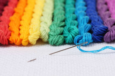 cornrows: sewing threads for embroidery and  needle with a thread on white cotton