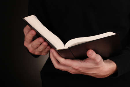 bible reading: Hands holding open russian bible on black background