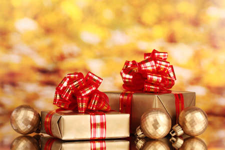 beautiful golden gifts with red ribbon and Christmas balls on yellow background Stock Photo - 11169681