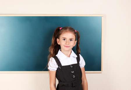 schooler: beautiful little girl standing near blackboard in the classroom Stock Photo