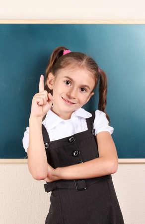beautiful little girl standing near blackboard in the classroom photo