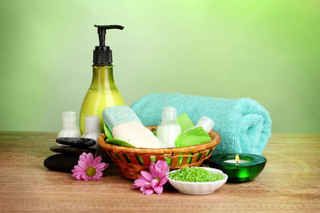 Hotel amenities kit in basket on wooden table on green background photo