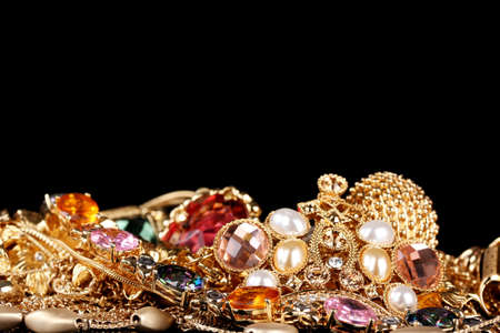 personal accessory: Various gold jewellery on black background