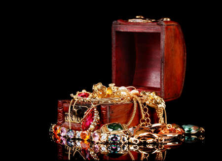 Wooden chest full of gold jewelry on black background Stock Photo - 11170043