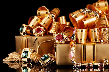 Various gold jewellery and gifts on black background photo