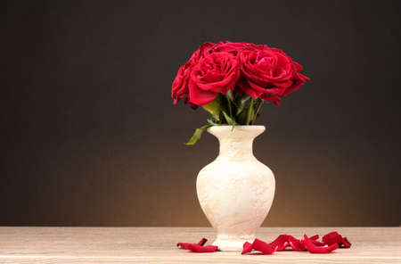 roses in vase: Beautiful red roses in vase on wooden table on brown background