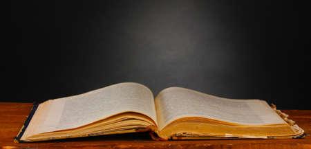 libros abiertos: viejo libro en la mesa de madera sobre fondo gris