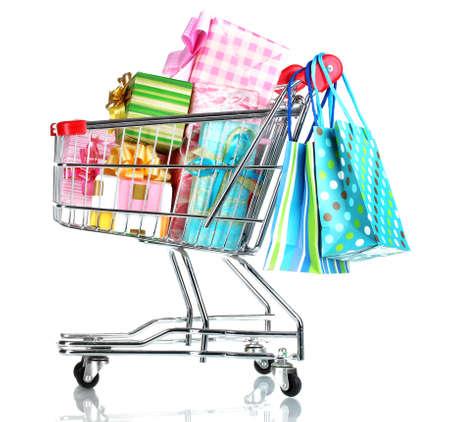 carrinho: carrinho de compras com os presentes brilhantes e sacos de papel isolado no branco Banco de Imagens