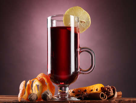grog: mulled wine in the glass, spice and lemon on purple background