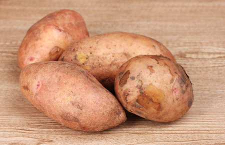 Potatoes on wooden background photo