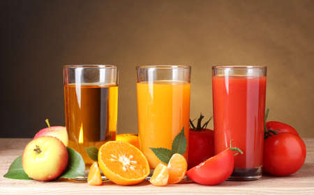 Different juices and fruits on wooden table on brown background photo