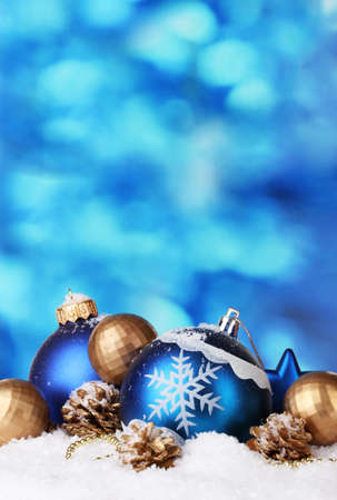 pine three: beautiful blue and golden Christmas balls and cones in snow on blue background