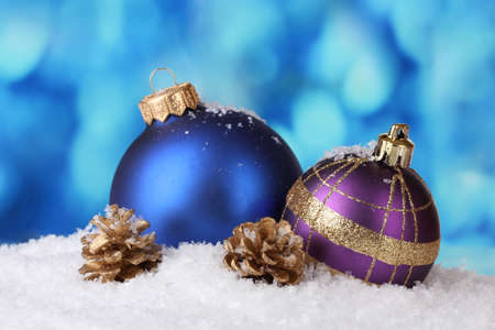 beautiful blue and purple Christmas balls and cones in snow on blue background photo