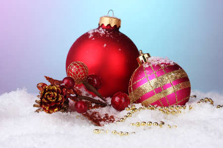 beautiful Christmas balls and cone on snow on bright background photo